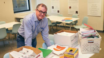 David Pfeifer standing over mail and other papers