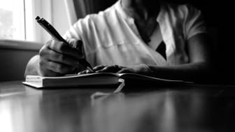 Torso of a man sitting at a table writing in a personal journal