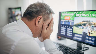picture of man in front of computer with his head in his hands after he lost an online bet