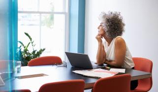 Woman sitting at a desk wondering