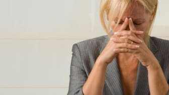 A distressed senior woman holds her hands to her face