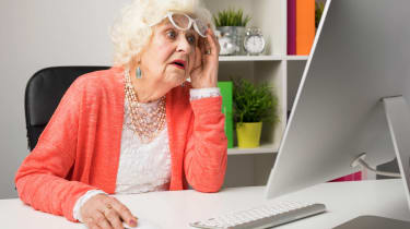 A grandma looks at her computer in dismay.