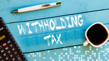"""Picture of """"withholding tax"""" written on blue wood"""