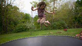 A girl bounces on a trampoline.
