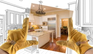Male contractor hands framing a photo of a kitchen update over sketches