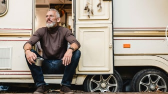 A senior man sits in the entryway to his RV