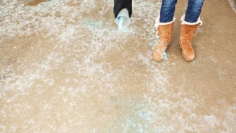 A woman is spreading blue ice melt (salt) on a frozen winter driveway. Focus is on the concrete surface, the hand is soft with some slight motion blur.