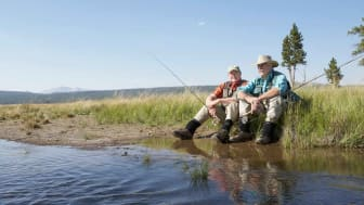 Two senior fly fisherman sit on the bank of a Montana river