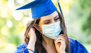 A college graduate wears a face mask and a cap and gown