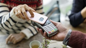 A woman uses her phone to make a payment in a store