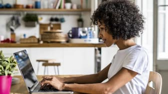 Woman using laptop at table at home