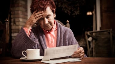 A senior woman looks distressed reading a bill at her kitchen table