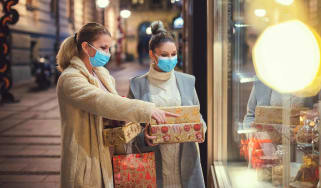 Two women shopping for the holidays wearing face masks.