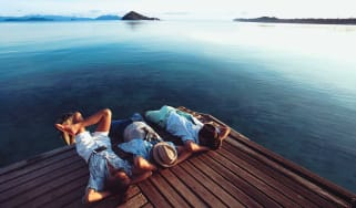 Three men lounging on a dock on a pretty lake