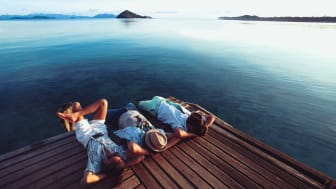 Three men kick back and relax on a dock at a lake
