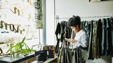 Smiling woman checking smartphone while shopping in boutique shop