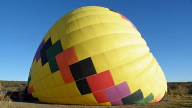 Brightly colored hot airballoon against blue sky. Ballon is partially inflated / deflated