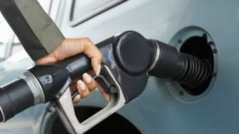 A hand holds a gasoline pump nozzle that's filling a car