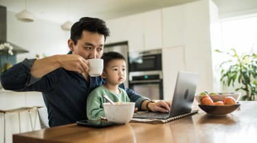 A man sips coffee as he works from the kitchen table with his little boy on his lap.