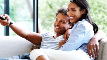 Happy young couple relaxing at home watching television
