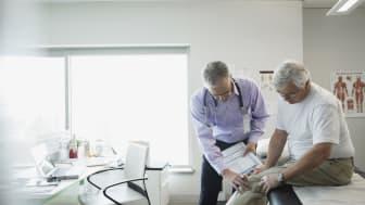 Doctor examining senior man۪s knee in examination room