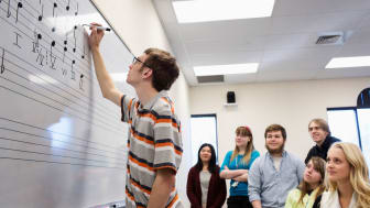 picture of music students writing musical notes on a classroom white board