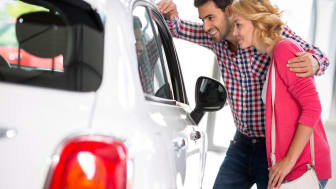 Youngcouple chooses to buy a car in car dealership saloon