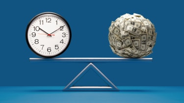 A clock is balanced by a ball of money on a fulcrum.