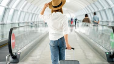 A woman in a straw hat walks through an airport toting a suitcase.