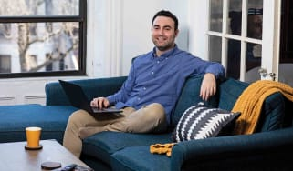 Stock trader David Nathanson sitting on a couch smiling at the camera.