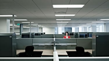 Businesswoman standing alone at cubicle in empty office