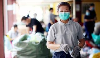 Senior woman volunteering wearing a health mask looking at the camera