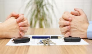 A man and a woman sit across one another with hands clasped on top of divorce papers.