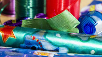 Various materials such as wrapping paper and ribbons to pack and decorate Christmas presents.