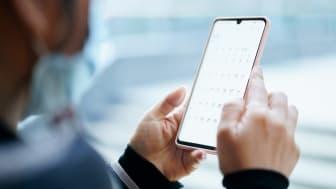 Man looks at calendar on his smart phone