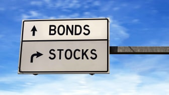 highway sign pointing to stocks and bonds