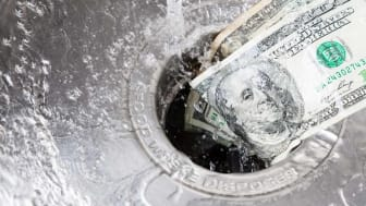 An image of cash money washing down the drain of a sink