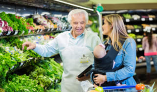Senior adult Caucasian man with gray hair is supermarket employee or produce manager. Man is assisting customer who is shopping for healthy food and fresh vegetables. Customer is mid adult Ca