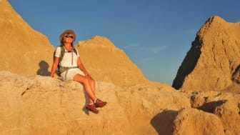 Senior woman sits on a ledge while hiking in the South Dakota Badlands