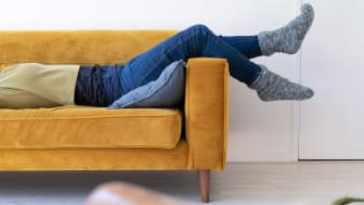 A woman lounges on a couch lazily.