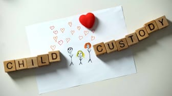 """picture of lettered blocks spelling """"child custody"""" with a child's drawing of her family"""