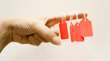 Price tags dangling from a woman's finger