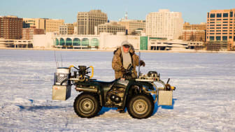 Senior fisherman with his ATV on frozen Lake Monona in Madison, Wisconsin, with the city as backdrop