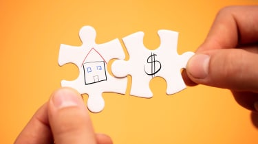 Two puzzle pieces, one with a drawing of a home on it and one with a dollar sign, fit together.