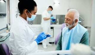 A dentist speaks with a patient.