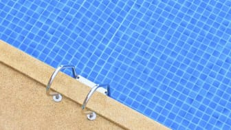 picture of edge of swimming pool with pool ladder