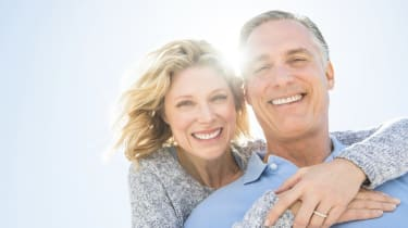 Cheerful Woman Embracing Man From Behind Against Sky