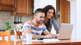 picture of a husband and wife looking at a computer in their kitchen