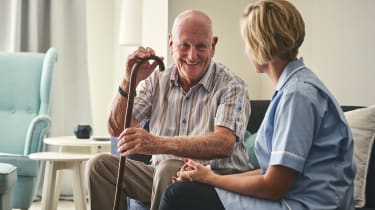 A nurse sitting with a patient in a nursing home.