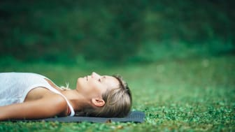 A woman lies in the grass, totally relaxed.